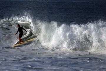 A surfer rides a wave at Punta Roca Beach in La Libertad