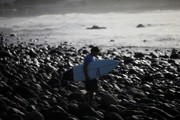 A surfer prepares to get in the water at Punta Roca Beach in La Libertad