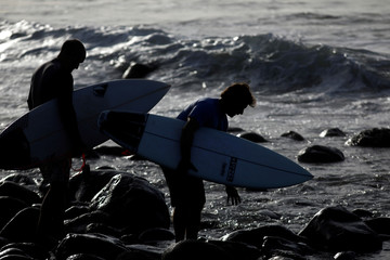 Two surfers prepare to get in the water at Punta Roca Beach in La Libertad
