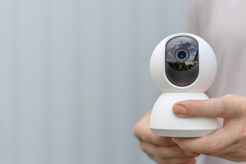 Man hold CCTV smart camera. 360 degree rotating security internet of things camera. Detection and video recording of crime. Automatic face recognition.