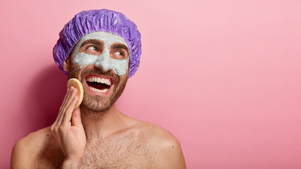 Relaxed smiling man cleans face with sponge, grooms himself, applies beauty mask, looks aside with glad expression, poses naked, wears protective shower cap, isolated on pink wall. Spa and grooming