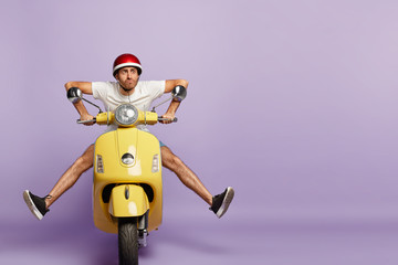 Funny young man with fasten motorbike helmet, poses on fast bike, wears white t shirt and sneakers, poses against purple background with empty space. People, transportation and riding concept