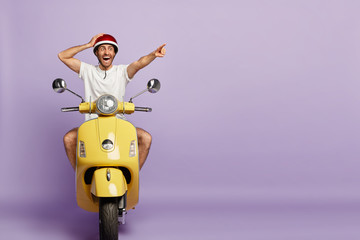 Surprised active man rides fast motorbike, points into distance, stares with shock, notices something incredible, wears protective helmet, isolated on purple background with blank copy space
