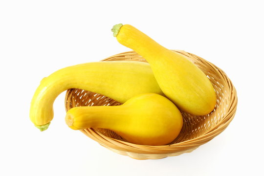 whole fresh yellow crookneck squash in basket on white background