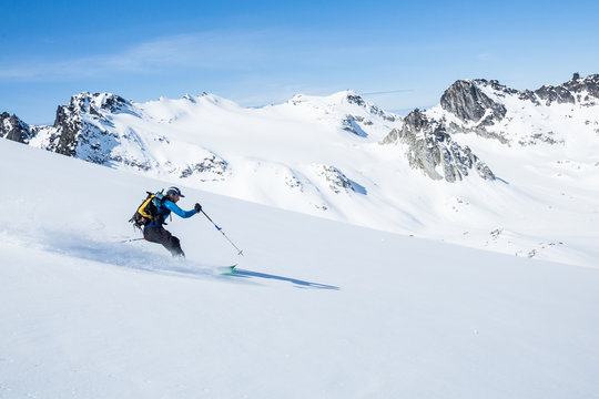 Skier on sunny slope of the Talkeetna Mountains in spring time. Fresh Alaska backcountry snow above the Snowbird Glacier.