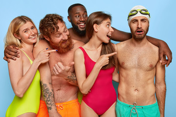 Crowd of cheerful diverse friends point at funny dejected guy in trunks, swimcap and goggles, laugh he cannot swim, enjoy holiday all together in resort place. Summer party and friendship concept