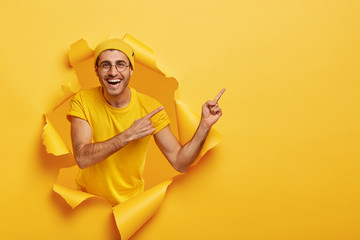 Handsome positive guy points away on right side, shows free space for your promotional information, stands in paper hole, wears yellow casual outfit and hat. People, advertisement, good mood concept
