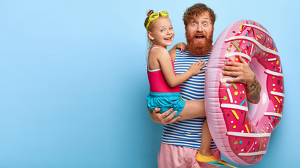 Photo of surprised father with thick ginger beard, happy small child on dads hands, wears protective goggles and fins, use donut swim ring, spend free time and have fun in water park, being on holiday
