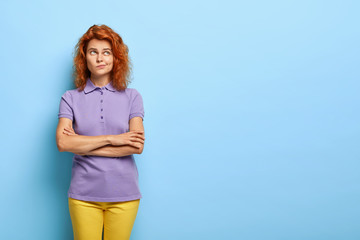 Perplexed pondering young woman with curly foxy hair, keeps arms folded over chest, purses lips and looks up, has doubts what to do better, needs good advice, dressed in casual apparel, poses indoor