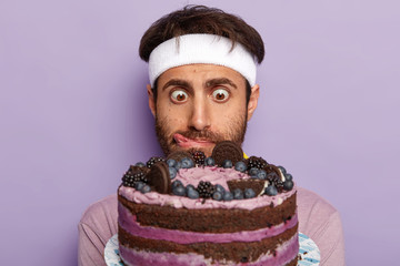 Close up shot of surprised guy stares at delicious cake, feels temptation, licks lips with tongue, wears white headband, tries go in for sport and refuse from junk food, isolated on purple background