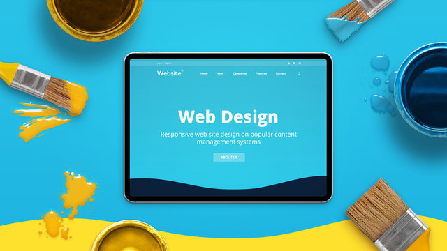 Web design concept with modern flat design theme on a thin tablet surrounded by color brushes and boxes. Top view, flat lay.