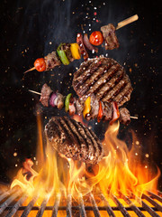 Tasty beef steaks and skewers flying above cast iron grate with fire flames. Freeze motion barbecue...