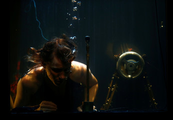 """Danish musician Nanna Bech performs underwater in a glass water tank during """"AquaSonic"""", a submerged musical performance, at the Malta International Arts Festival in Valletta"""