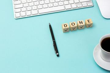 """Aufgabe, Planung, Konzept erledigt. Würfel mit dem Wort """"done"""" auf dem Schreibtisch ."""