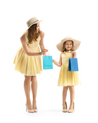 Portrait of beautiful woman and her little daughter with shopping bags on white background