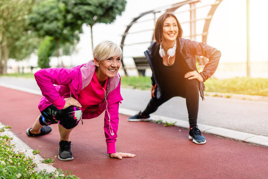 Happy mature woman with her daughter exercising together in park.