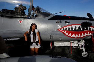 A girl poses for a photo next to T-27 Super Tucano aircraft during the F-Air Colombia 2019 air festival in Rionegro