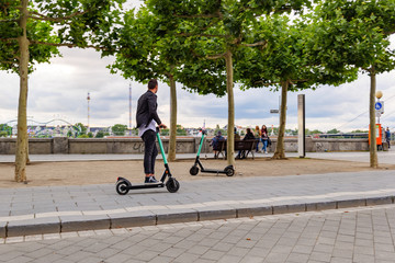 People use and ride E-scooters, trendy urban transportation with Eco friendly mobility concept of sharing Electric Scooter, at promenade riverside of Rhine River.