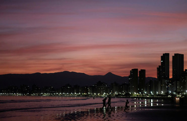 People walk on a beach during sunset in Praia Grande
