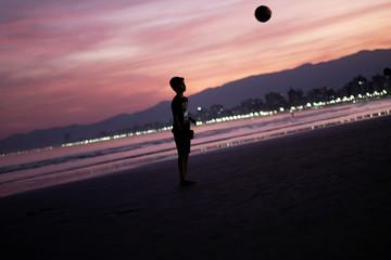 Boy plays on a beach during sunset in Praia Grande