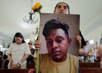 A relative holds a picture of Francisco Flores during a religious service to commemorate the first anniversary of the death of protesters who died during the attack on the Divine Mercy Church