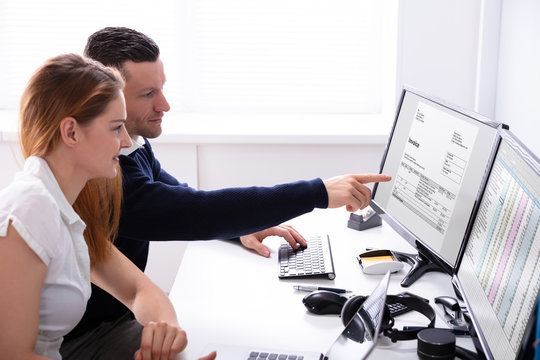 Businessman Pointing Invoice On Computer Screen