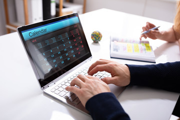 Fototapete - Businessperson's Hand Using Laptop With Calendar On Screen