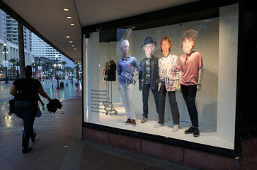 A woman walks past mannequins featuring the faces of The Rolling Stones in New Orleans