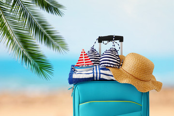 Wall Mural - holidays. travel concept. blue suitcase with female hat, bikini, sailing boat and beach towel in front of tropical background