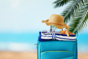 Wall Mural - holidays. travel concept. blue suitcase with female hat, starfish, sunglasses and beach towel in front of tropical background