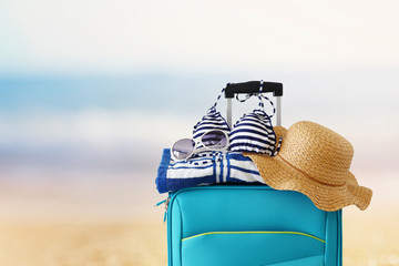 Wall Mural - holidays. travel concept. blue suitcase with female hat, sunglasses bikini and beach towel in front of tropical background