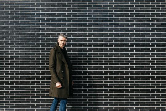 Trendy man in khaki coat over brickwall.