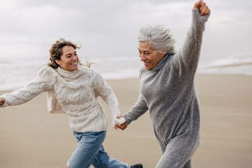 Active senior woman and her daughter enjoying on the beach in winter.