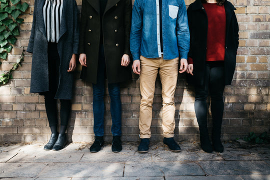 Crop of four people in casual clothes over brick wall.