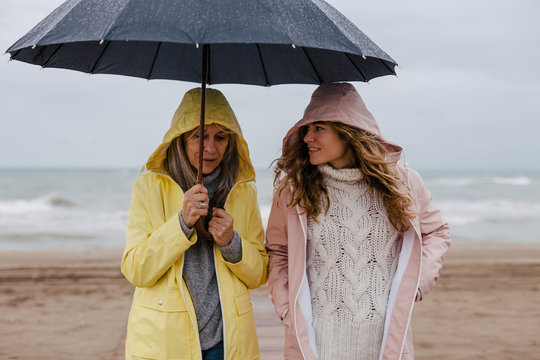 Senior woman and her daughter holding an umbrella in a rainy day on the beach.