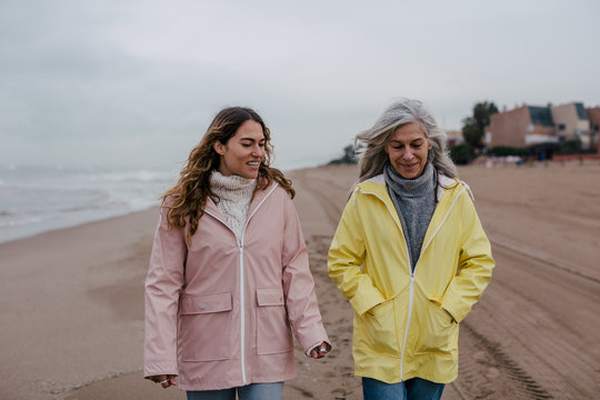 Senior woman and her daughter walking on the beach in a winter day.