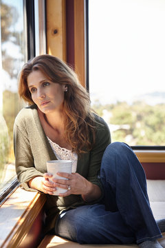 Depressed woman looking out the window in her home