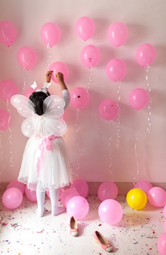 Little girl on her birthday dressed with butterfly wings decorating with ballons and ribbons