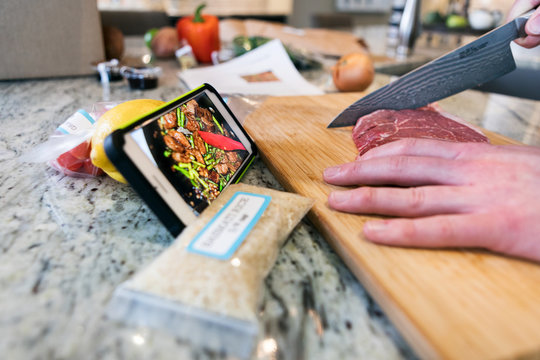 Meal: Man Watches Video Instructions While Cutting Steak