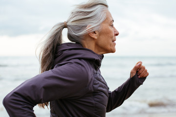 Side view of senior woman running on beach