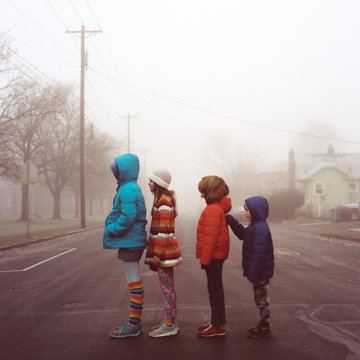Four kids in height order standing in a street on a foggy morning in Portland, Oregon.