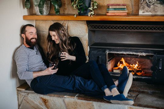 Happy Couple Sitting by Fireplace Drinking Wine