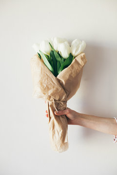 Female hand holding tulip bouquet in front of a white background