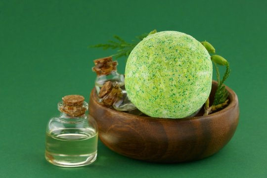 bath bombs and thuja essential oil.  natural essential oil in glass bottles set and a green bomb for a bath, a sprig of thuja on a dark green background. Set for aromatherapy and relaxation