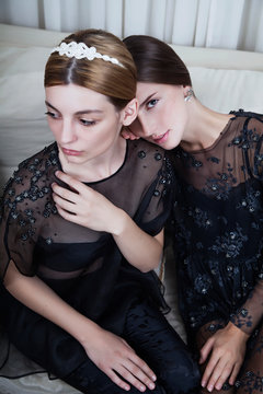 Two beautiful women sitting on the couch in black dresses