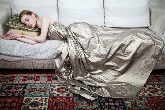 Young beautiful woman in a dress lying down