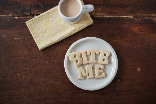 "Shortbread Cookie Letters spelling out the words """"bite me"""" during a tea break"