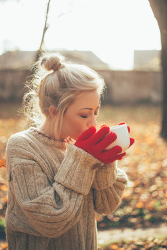 A young woman drinks a hot drink in the winter.