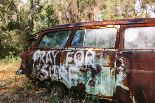 Pray For Surf spray painted on an old rusted classic car