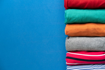 close up of rolled colorful clothes on blue background Fototapete